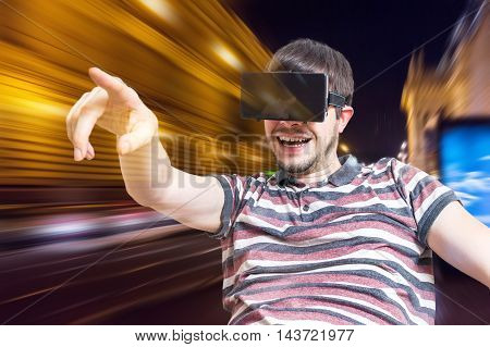 Young man is wearing 3D virtual reality headset and is playing videogames.