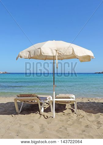 White sunshade and beach chairs on the beach, with view to turquoise sea.