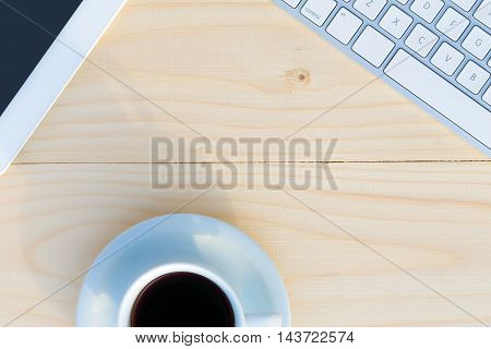 Image of Light Wooden Table with Computer Keyboard Cropped Tablet and Coffee Mug from above
