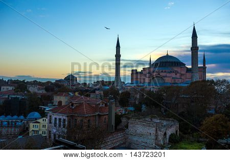 Famous Attractions of Istanbul Turkey Sophia Cathedral and Old City Istanbul District with Minarets buildings at sunrise blue orange Sky and Clouds Sea Gull flying