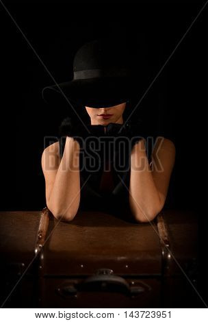 Fashion photo of beautiful lady in elegant black hat. Gorgeous, attractive, sensual, elegant, classical girl, model in black dress, black gloves sitting on black chair on black background with bag