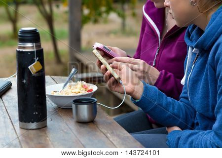 Rural vacation Scene Two People sitting at Wood Table with healthy Food Breakfast and Travel Thermos holding mobile telephones sharing and talking
