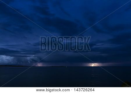 Thunderstorm at sea. Summer night, lights from an inlet and lightning flash from a thunderstorm.