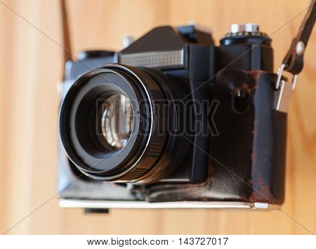 Old Camera In A Leather Case Hanging On Wooden Wall