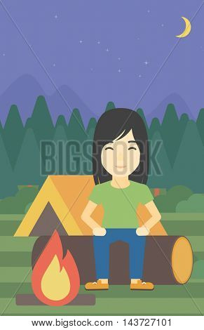 An asian woman sitting on a log near a fire on a background of camping site with tent. Woman sitting near a campfire at a campsite. Vector flat design illustration. Vertical layout.