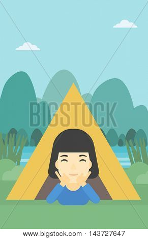 An asian woman crawling out from a camping tent. Travelling woman with her hands on cheek lying in camping tent and relaxing. Vector flat design illustration. Vertical layout.