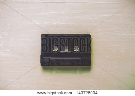 Old audio cassettes on green wooden background