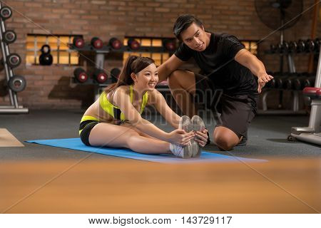 Smiling sporty girl exercising with trainer in gym