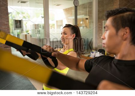 Asian sporty people exercising with trx in gym