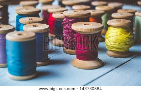 Set of reels with colorful threads on wooden background