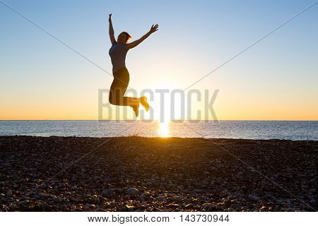 Silhouette of jolly Woman jumping high with arms raised on Ocean Beach with Sunrise on background