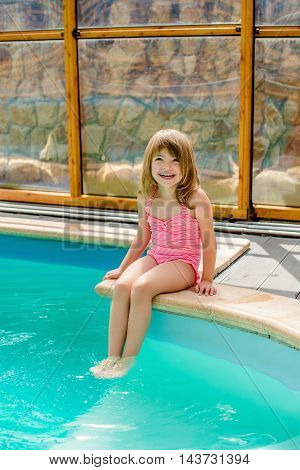 The little girl in a bathing suit sitting at the pool
