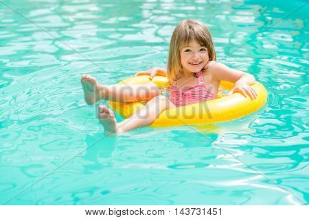 Happy little girl floating in the pool to rescue circle yellow
