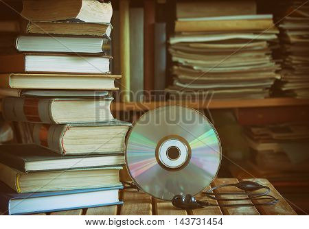 stack of book  library cd headphones wooden table and bookcase