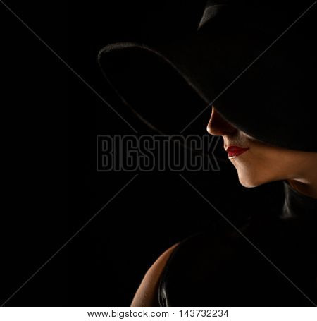 Portrait of beautiful girl in hat in profile,posing in studio,black and white photography. Beauty Woman face Portrait in black hat.Isolated on dark background.Female looking aside.Profile silhouette