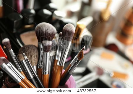 Set of make-up brushes and decorative cosmetics on blurred background