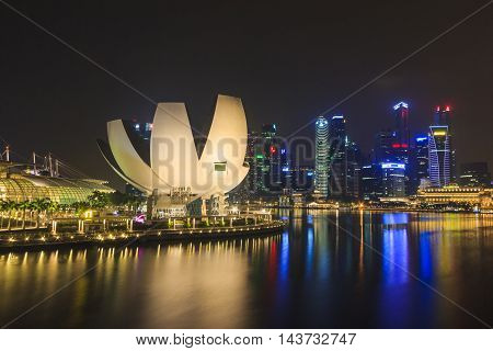 SINGAPORE SINGAPORE - SEPTEMBER 28 2013 : Night view of the Art Science Museum in front of Marina Bay Sands located at Marina Bay a famous tourist attractions in Singapore.