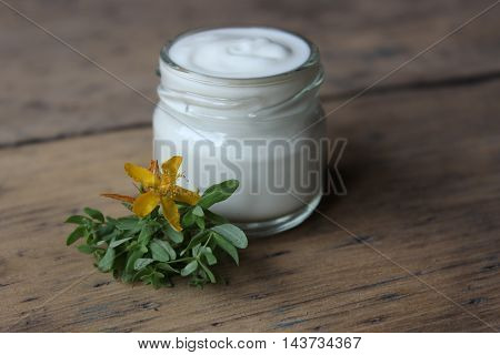 Organic face cream with flower hypericum on wooden boards