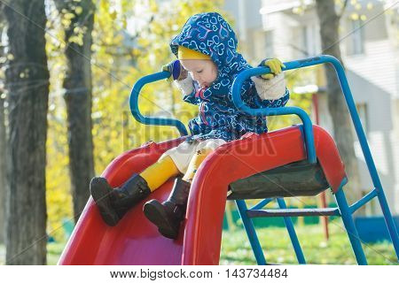 Concentrated girl in warm hooded jacket is sliding down red plastic playground slide at yellow autumn tree leaves background