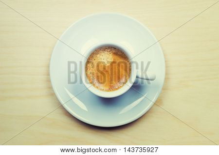 Vintage cup of espresso on wood background