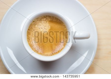 White cup of espresso on wood background