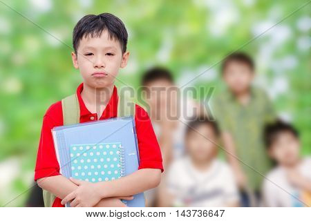 Unhappy asian school boy at school with friends in background