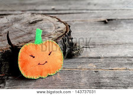 Halloween pumpkin crafts isolated on wooden background. Homemade sewing crafts for kids and beginners. Halloween abstract pumpkin