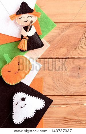 Halloween cute felt ornaments. Home made small witch with broom, pumpkin head, ghost. Halloween crafts, colored felt pieces on wooden background with blank space for text. Autumn kids crafts