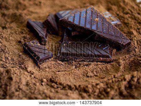 Dark chocolate on cocoa powder, strip surface