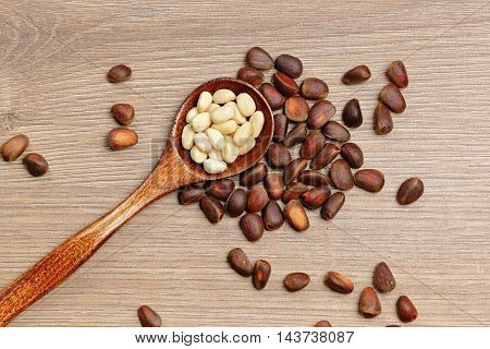 Pine nuts and spoon closeup on wooden background