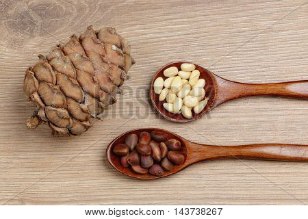 Pine nuts in a spoon and a pine cone closeup on wooden background
