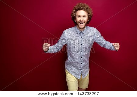 Portrait of happy smiling curly-haired man in bow-tie emotionally spreads his arms. Isolate. Yellow background.