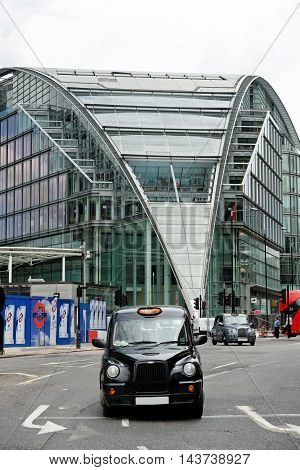 LONDON ENGLAND - JULY 8 2016: A black cab at Cardinal Place - a retail and office development near Victoria Station. The site consists of three buildings covering over a million square feet on Victoria Street.
