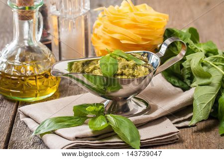 Basil pesto sauce in metal gravy boat and fresh ingredient on wooden background