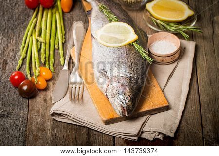 Fresh trout with vegetables, spices and seasoning on cutting board
