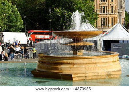 LONDON ENGLAND - JULY 8 2016: Fountains on Trafalgar Square. It is a public square in the City of Westminster Central London built around the area formerly known as Charing Cross.