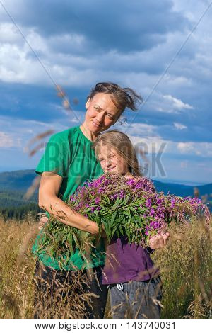 Smiling mom and daughter hugging in a alpine meadow in lush grass on the background of a stormy sky.