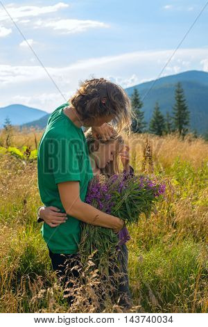 Dreaming mom and daughter are hugging on alpine meadow among the lush herbs on the background of a blue sky and mountains at sunny day.