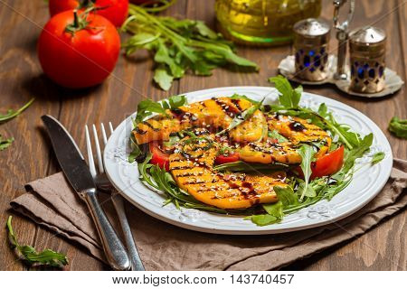 Delicious grilled pumpkin and arugula  salad on white plate over wooden background