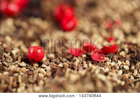 whole, crashed and ground black and red peppercorns background