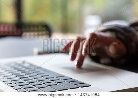 Close up Image of Computer and Hand of Person scrolling Touchpad with focus on keyboard and Hotel Cafe Interior on Background