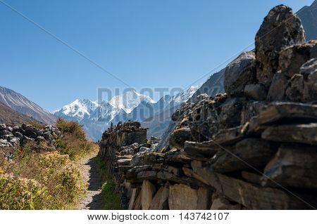 Mani Wall in Langtang Valley with Langshisa Peak (Langshisha Ri) Langtang National Park Rasuwa District Bagmati Nepal.