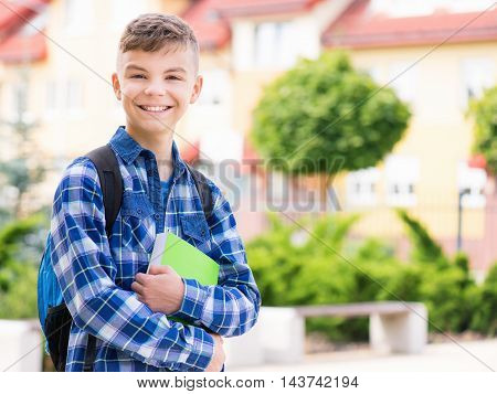 Outdoor portrait of happy teen boy 12-14 years old with books and backpack. Young student beginning of class after vacation. Back to school concept.
