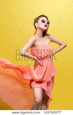 fashion photo of beautiful young woman in nice clothes with pin-up make-up and hairstyle posing over yellow background.