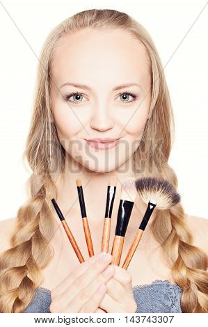 Cute fashion beautiful woman holding makeup brushes