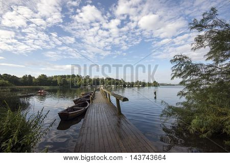 Small Wooden Bridge and Boats on Faarup Lake in Denmark