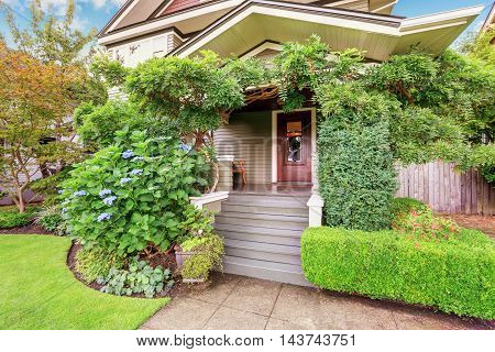 Cozy Covered Porch Sinking In Green Bushes And Trees.