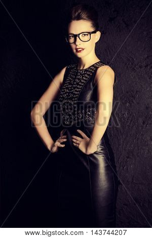 Attractive young woman alluring in black leather dress over black background. Beauty, fashion. Business style.