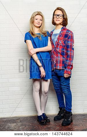 Two modern teenage boy and girl standing together by a brick wall. Friendship. First love. Full length portrait.