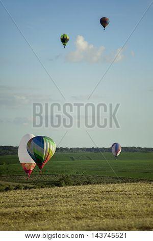 Balloons start fly on fields, hills in summer